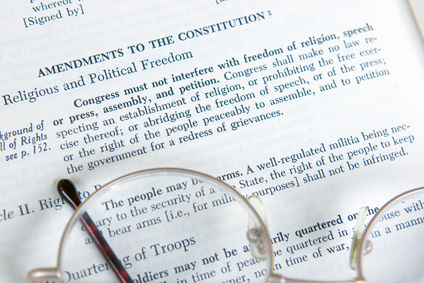The First Amendment to the Constitution is shown on the page of a history book.