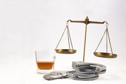 DUI lawyer concept of miniature car with alcohol bottle, handcuffs and legal scales