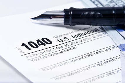 Tax form 1040 on a gray background, blue pen, and 100 dollar bills out of focus